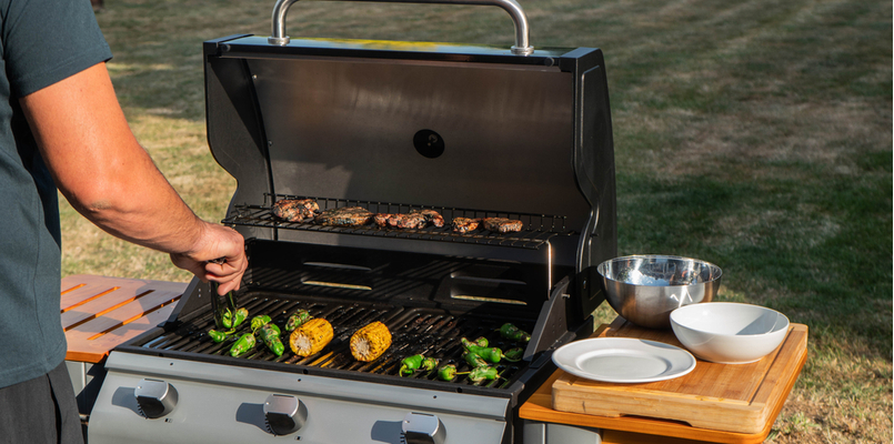 Person grilling food on barbecue outside