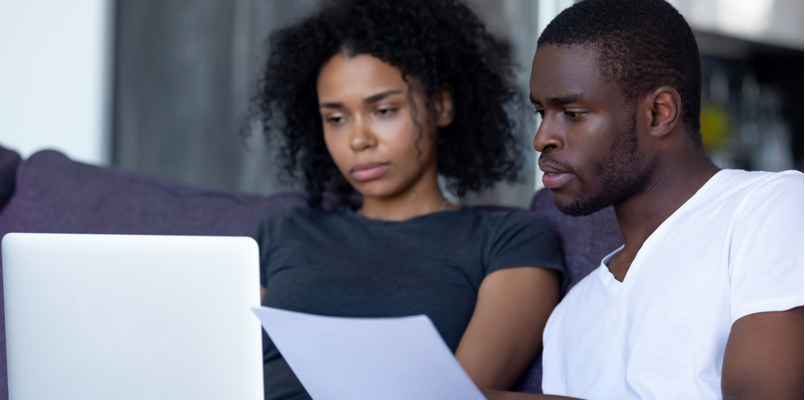 serious couple reading document and looking at laptop