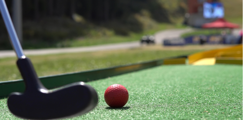 player playing mini golf with a red ball